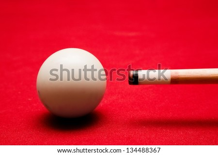 Billards pool game. Aiming at cue ball. Red cloth table - stock photo