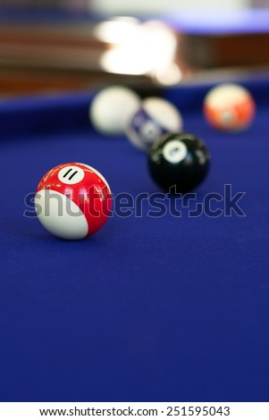 Billiard balls on a purple fabric pool table. Shallow depth of field with sharpest focus on the 11 ball. - stock photo
