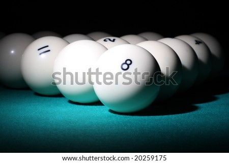 "Billiard. Balls pyramid with number 8 ball on a foreground. Selective focus on a 8ball. ""Low-key"" scene. - stock photo"