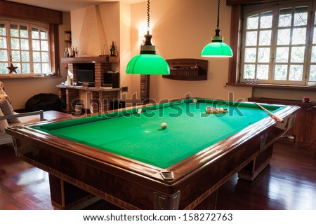 Billiard table with mock tiger skin rug on parquet floor - stock photo