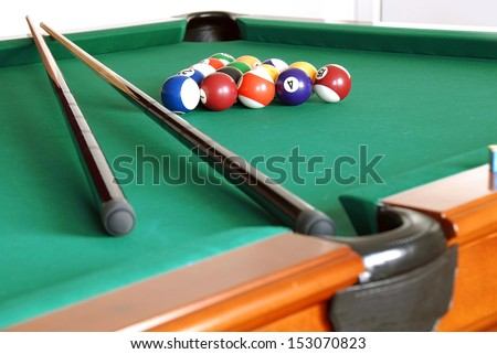 billiards table with balls and cues - stock photo