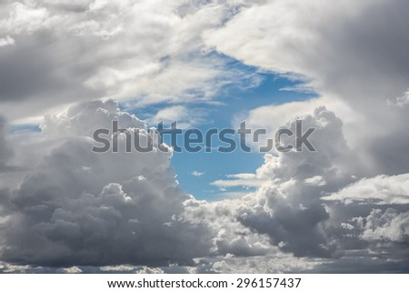Billowing storm clouds with moisture rich dark bottoms surround a patch of blue sky in early Spring. - stock photo