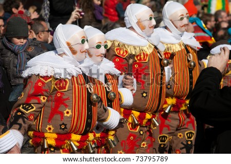 BINCHE, BELGIUM - MARCH 8: Gilles in mask performs round dance at Carnaval de Binche on March 8, 2011 in Binche, Belgium. Carnival in Binche is included in a list of intangible heritage by UNESCO. - stock photo