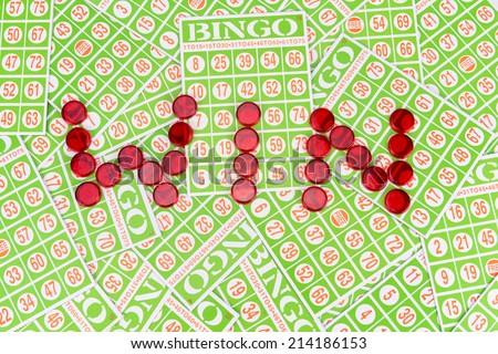 "bingo chip arrange in ""win"" word on bingo card background - stock photo"
