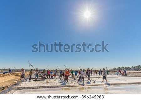 Binh Thuan, Vietnam - January 22nd, 2016: Group Fishermen rhythmic scraping salt heaps, above the radiating sun shines for stars such as fishermen in morning coastal location of Binh Thuan, Vietnam - stock photo