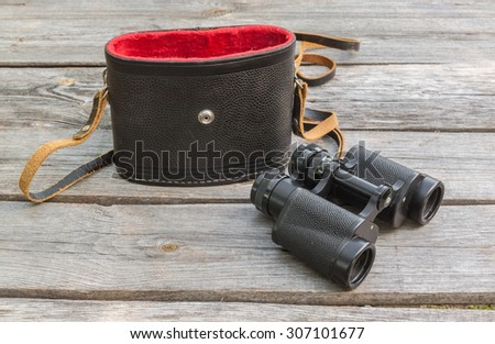 Binocular and the case on wooden table. - stock photo