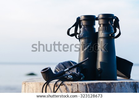Binocular and vintage pipe with tobacco pouch - stock photo