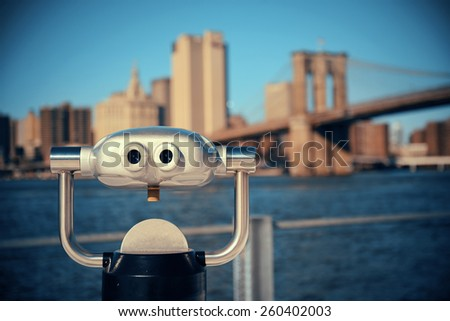 Binocular at waterfront with Brooklyn Bridge and skyscrapers. - stock photo