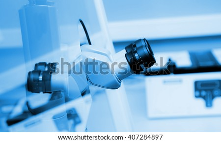 binocular microscope behind a sefety glass in a laboratory, grinish collored photo. - stock photo