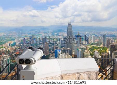 Binoculars and Kuala Lumpur (Malaysia) city view - architecture background - stock photo