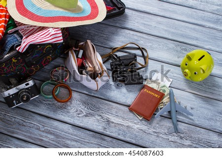 Binoculars and suitcase with clothes. Piggy bank and toy plane. Luggage and document for journey. Things on gray wooden floor. - stock photo