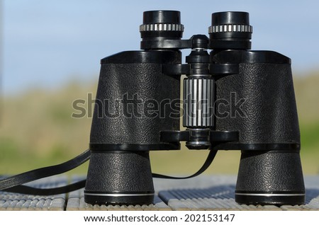 Binoculars field glasses against blue sky. Concept photo of adventure, search and exploring outdoor.  - stock photo