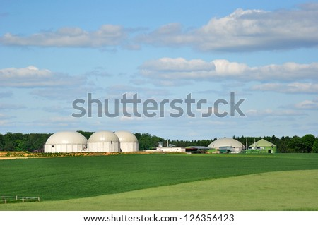 Bio fuel plant with forest in background. - stock photo