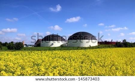 Bio gas plant in a rape field - stock photo