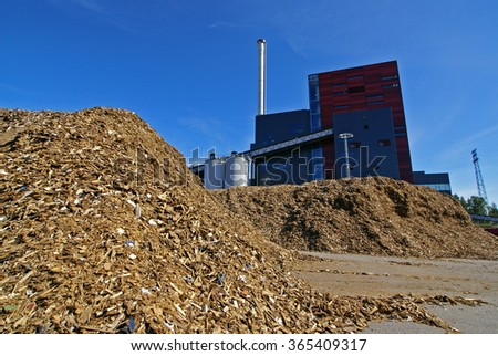 bio power plant with storage of wooden fuel (biomass) against blue sky - stock photo