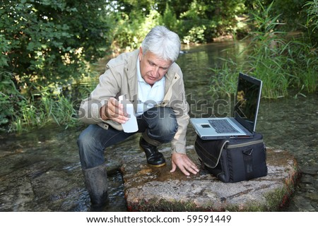Biologist testing quality of stream water - stock photo