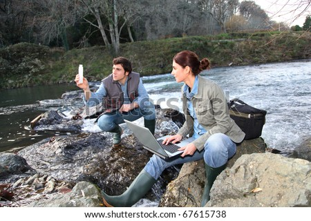 Biologists testing water of natural river - stock photo