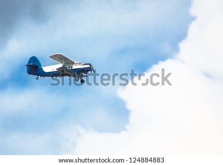 Biplane in blue Sky over clouds - stock photo
