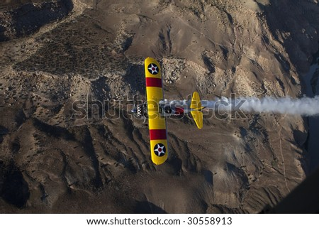 biplane top view over desert with smoke - stock photo