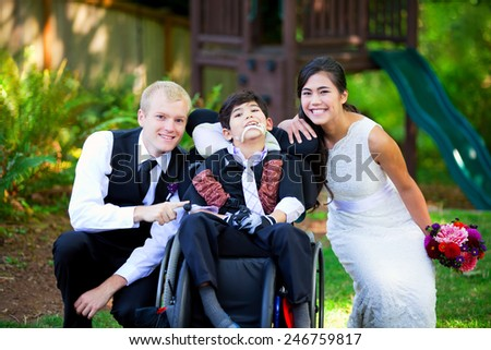 Biracial bride and groom with her little disabled brother in wheelchair on their wedding day - stock photo