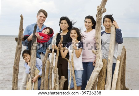 Biracial family together at the beach in summer - stock photo