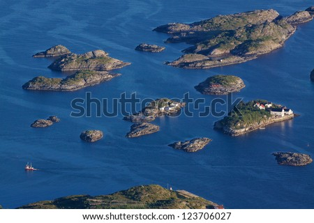 Bird eye view of fishing boats sailing between scenic islets near Henningsvaer on Lofoten islands in Norway - stock photo