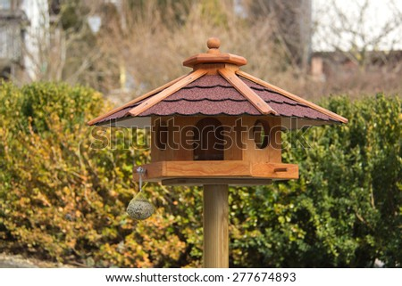 Bird feeder house / Bird feeder house with bird food - stock photo