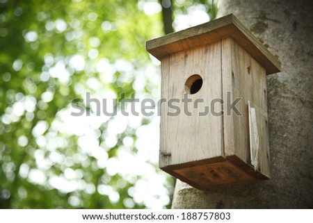 Bird house hanging from the tree with the entrance hole in the shape of a circle. - stock photo