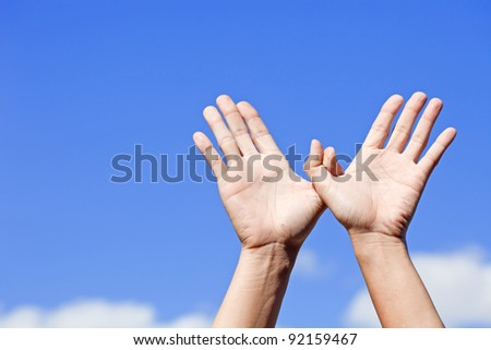Bird made of hands over the blue sky - stock photo