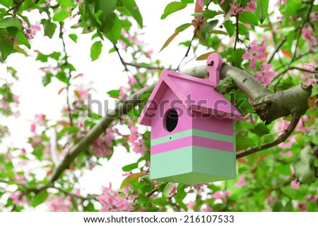 Birdhouse in garden outdoors - stock photo