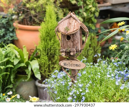 birdhouse nestles among spring flowers - stock photo