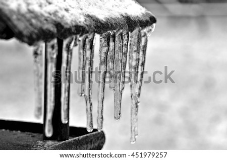 Birdhouse with icicles on a gray background in black and white - stock photo