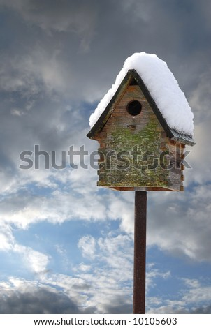 Birdhouse with snow on roof - stock photo