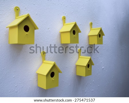 Birds houses hanging on the white wall - stock photo