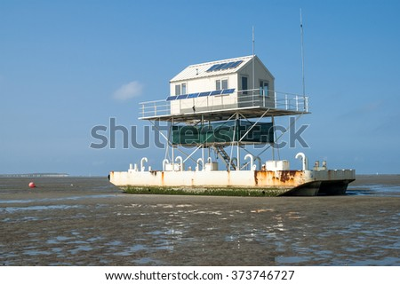 Birdwatch cabin on the tidal flats at low tide of the wetlands, Wadden Sea, Netherlands - stock photo