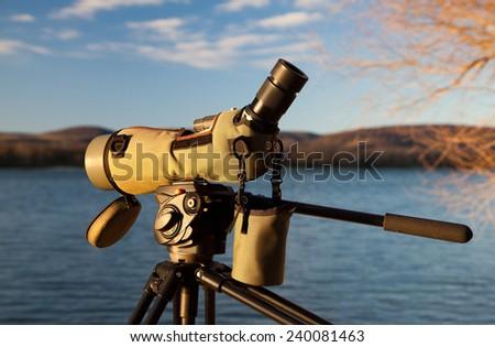 Birdwatching monocular or spotting scope on a tripod near water - stock photo