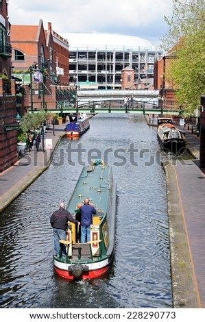 BIRMINGHAM, UK - MAY 14, 2014 - Narrowboats at Brindley Place with Old Turn Junction and the National Indoor Arena to the rear, Birmingham, West Midlands, England, UK, Western Europe, May 14, 2014. - stock photo