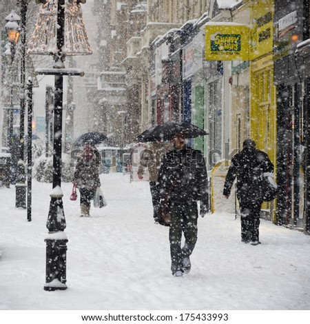 BIRMINGHAM, UNITED KINGDOM - NOVEMBER 18, 2010: People walking in Colmore row, Birmingham during the 2010 winter snow storm which brought chaos across the UK. - stock photo