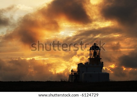 Birsay Lighthouse, Orkney, in silhouette at sunset - stock photo