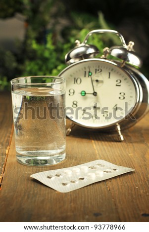 Birth control pills and a glass of water on a bedside table - stock photo
