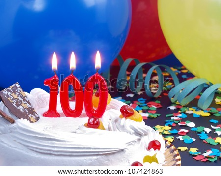 Birthday-anniversary cake with red candle showing Nr. 100 - stock photo
