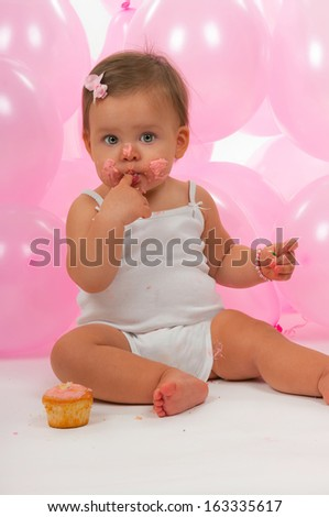 Birthday baby eating her birthday cupcake - stock photo