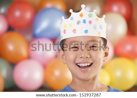 Birthday Boy Wearing a Crown in Front of Balloons - stock photo