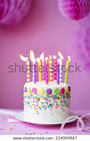 Birthday cake against a party background - stock photo