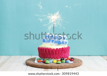 Birthday cake decorated with a sparkler on blue background - stock photo