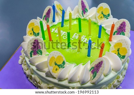 Birthday cake lit with many color candles. - stock photo