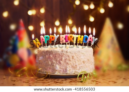 Birthday cake with candles, bright lights bokeh. - stock photo