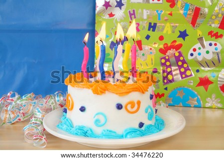 Birthday cake with candles lit and packages in the background with room for your text. Used a shallow depth of field and selective focus being on the lit candles. - stock photo