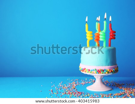 Birthday cake with candles on blue background. - stock photo