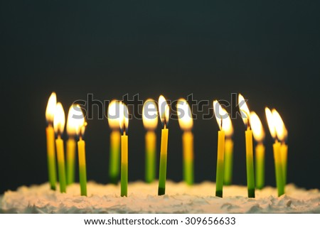 Birthday cake with candles on dark background - stock photo